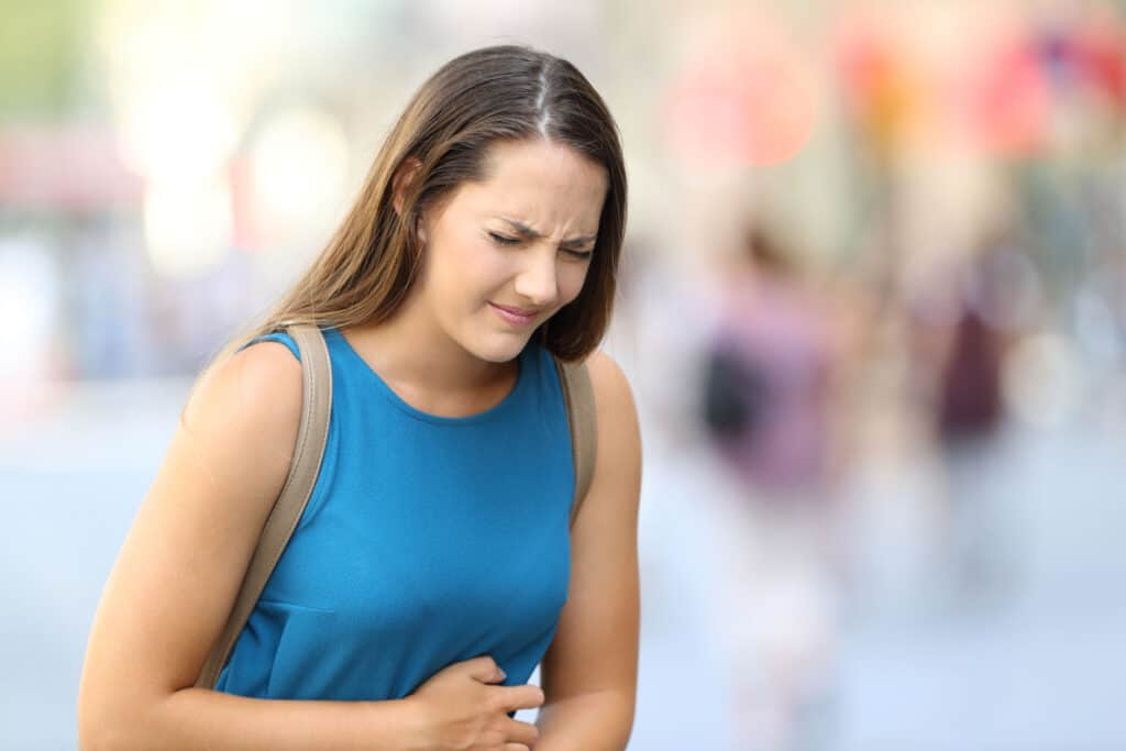 Single woman suffering belly ache outdoors in the street